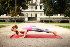 Muscular and strong yoga woman trainee exercising workout in city park